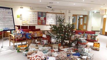 Weihnachtsbaum, geschmückt, mit Geschenken davor.